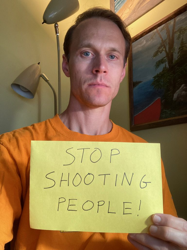 "Kenneth holding a sign that says ""Stop Shooting People!"""